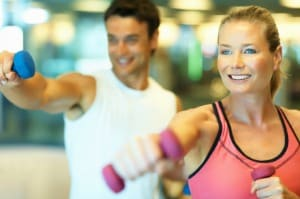 Focus on woman working out with hand weights with man in background